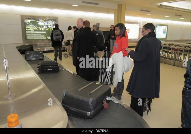 Washington DC Ronald Reagan Washington National Airport DCA terminal baggage claim carousel luggage Black woman - Stock Image