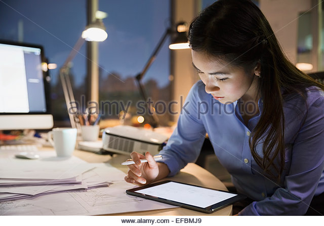 Businesswoman with digital tablet working late in office - Stock-Bilder