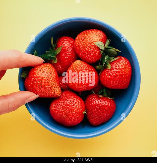 Woman's fingers grabbing a strawberry from a bowl - Stock Image
