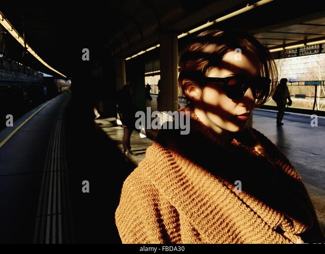 Close-Up Of Woman In Sunglasses Standing On Railroad Station Platform - Stock Image