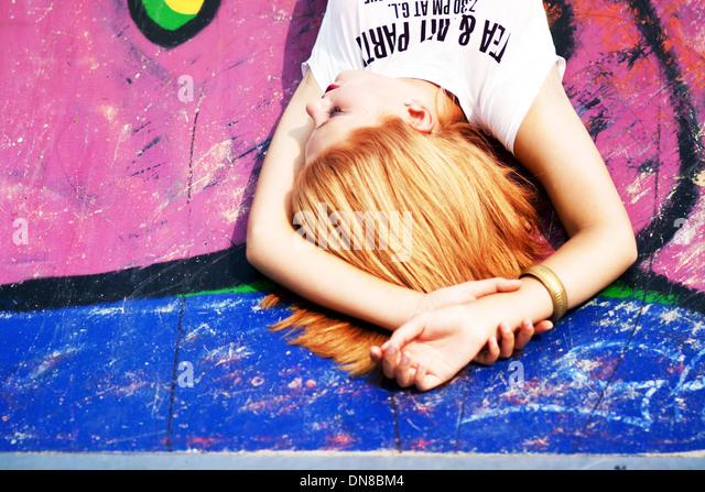 Woman lying on floor with graffiti - Stock Image