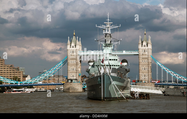 Tower Bridge London with HMS Belfast ship under a dramatic sky Summer 2013 - Stock Image