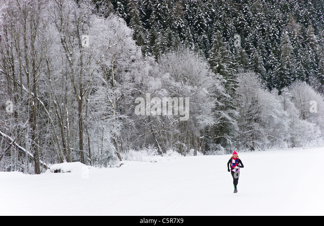 A jogger runs on snow field past snow covered winter landscape. - Stock-Bilder