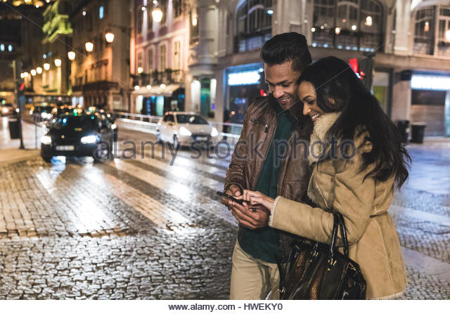 Couple in city, at night, looking at smartphone, Lisbon, Portugal - Stock-Bilder