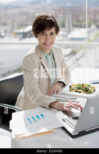 Portrait of smiling businesswoman eating lunch and working at desk - Stock Image