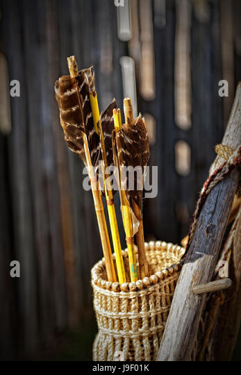 Three handmade arrows in a straw quiver. - Stock Image