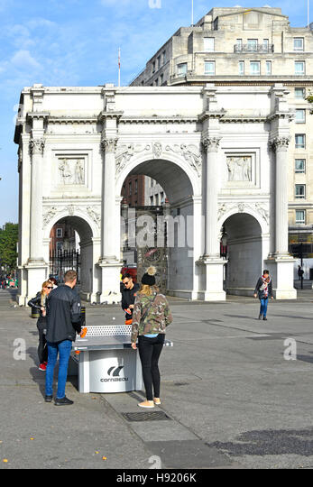 Table Tennis Ping Pong table tourists playing game on outdoor table in front of Marble Arch triumphal arch in London - Stock Image