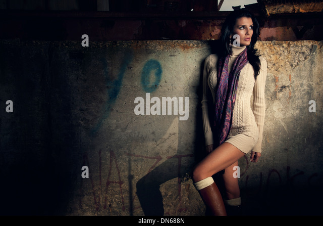 Fashion portrait of woman standing in abandoned warehouse in short dress - Stock Image