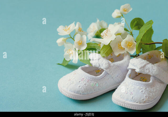 Cute, White Vintage Leather Infant Baby Shoes with spring flowers on Cyan Background and room or space for copy, - Stock Image