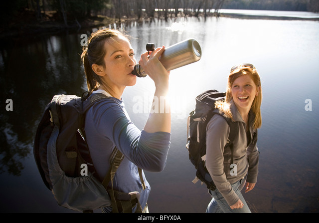 Two women sharing water beside lake - Stock Image