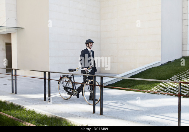 Mid adult businessman walking with bicycle - Stock Image