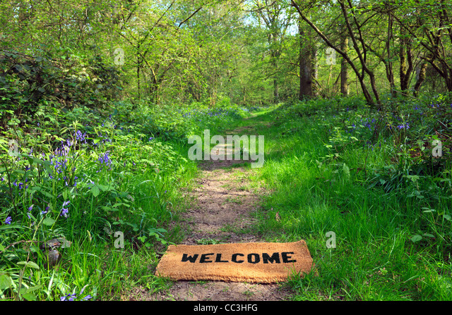 Concept photo of a Welcome doormat on a woodland footpath during springtime in horizontal format. - Stock-Bilder