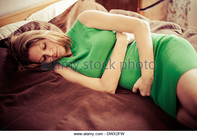 Pregnant woman holding belly while resting in bed - Stock Image