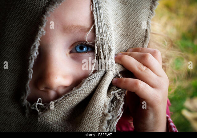 Portrait of girl (4-5) hiding face behind curtain - Stock Image