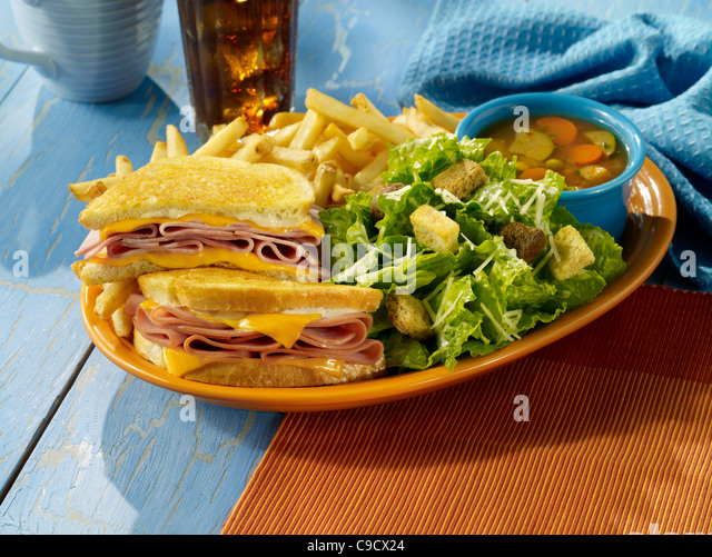 A grilled ham and cheese sandwich with a caesar salad, fries, a cup of soup and a glass of ice tea - Stock Image