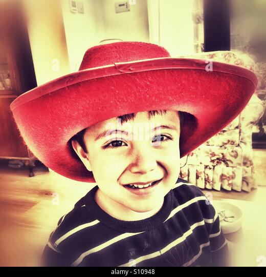 A happy young boy in a red hat. - Stock Image