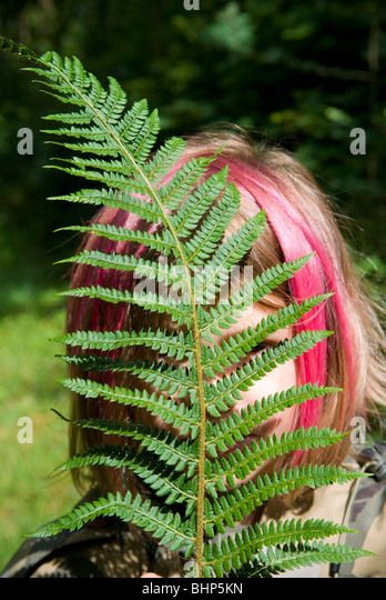 a young girl with pink dyed hair in bob hides behind a bright green fern leaf that partly obscures her face - Stock Image