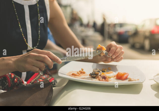 A young woman is having a traditional English breakfast at a table outside a cafe on the street - Stock Image