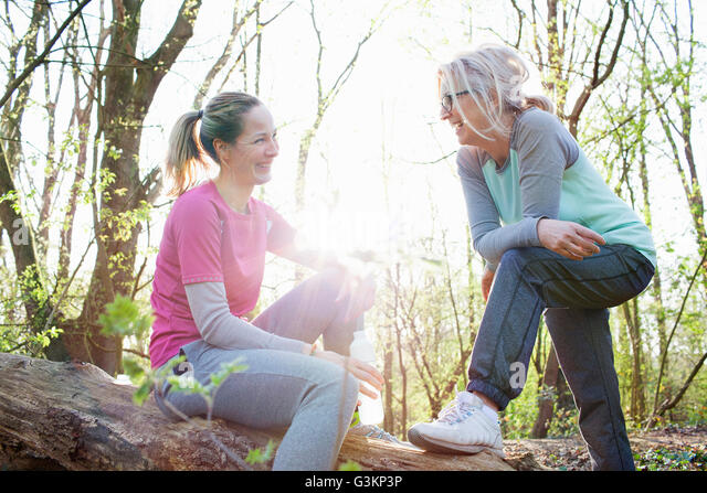 Women in forest sitting on fallen tree face to face smiling - Stock Image