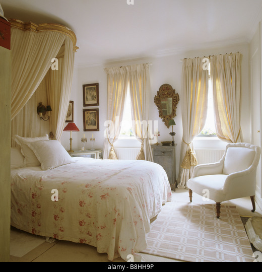 Traditional bedroom with a feminine feel, corona and muslin bedhangings and a gilded Italian 18th century mirror - Stock Image