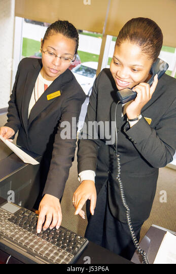 Little Rock Arkansas The Peabody Little Rock hotel lobby Black woman women young work job business suit staff front - Stock Image