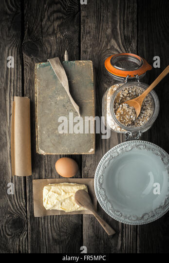 Recipe book, plate and ingredients for cookies on a wooden table vertical super still life - Stock Image