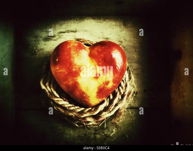 Red glass heart with a rope - Stock Image