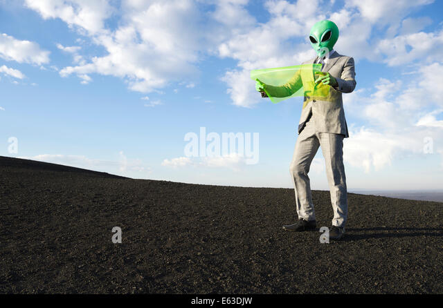 Explorer alien businessman in lunar landscape reading electronic map on future technology flexible display tablet - Stock Image