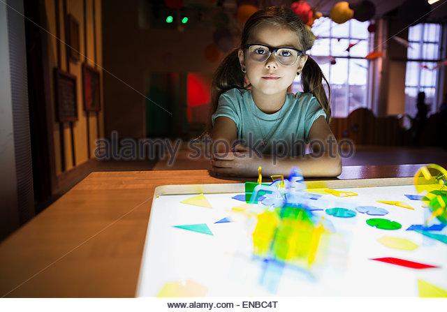 Portrait confident girl assembling geometric shape science center - Stock Image