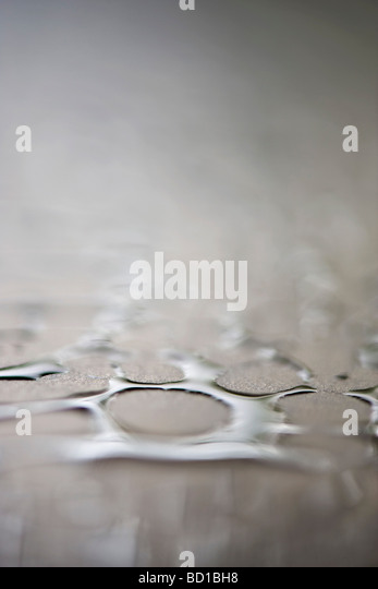 Water droplets on surface, extreme close-up - Stock-Bilder