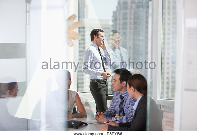 Businessman talking on cell phone in meeting - Stock-Bilder
