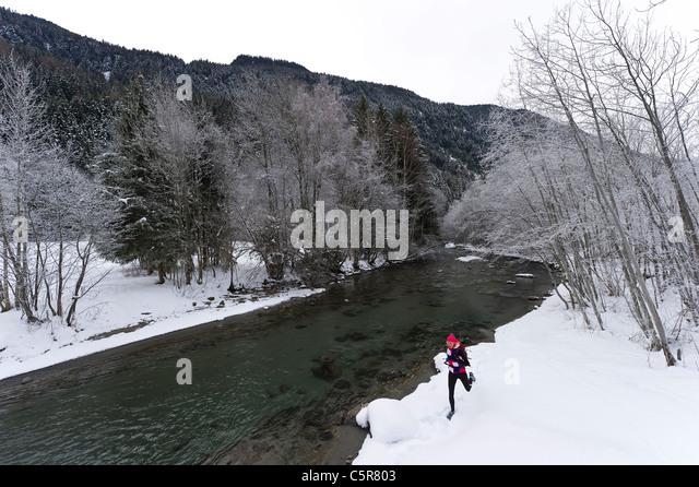 A jogger running alongside a snowy river. - Stock-Bilder
