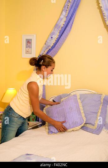 Brazilian American teenager girl tidying up making her bed.California MR ©Myrleen Pearson - Stock-Bilder