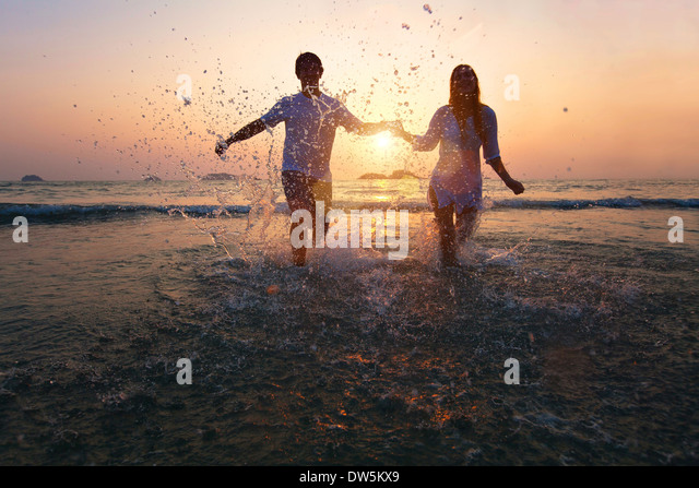 happy couple enjoy sunset on the beach - Stock Image