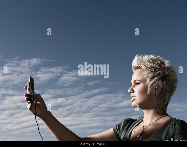 Woman looking at mobile phone, wearing headphones, backgrounded by dusk sky - Stock-Bilder