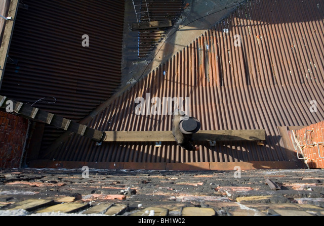 Chimney sweep on corrugated iron roof, Berlin, Germany - Stock Image