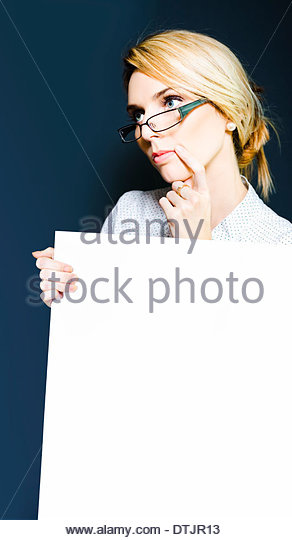 Attractive blonde business girl standing in office contemplating your message after you place it on the blank poster - Stock Image