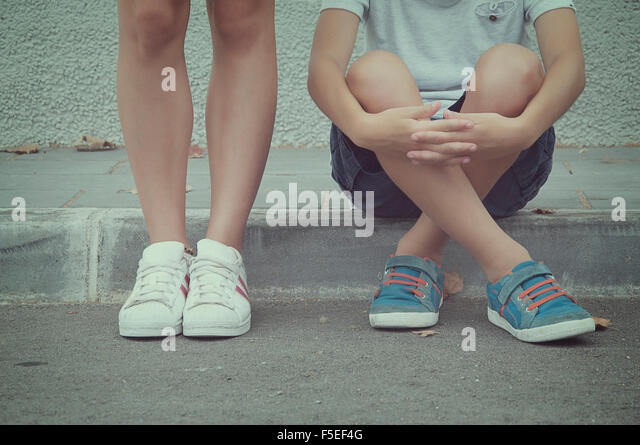 Close-up of two teenagers sitting and standing in the street - Stock Image