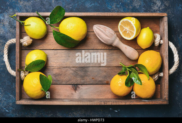 Freshly picked lemons with leaves in wooden box - Stock Image