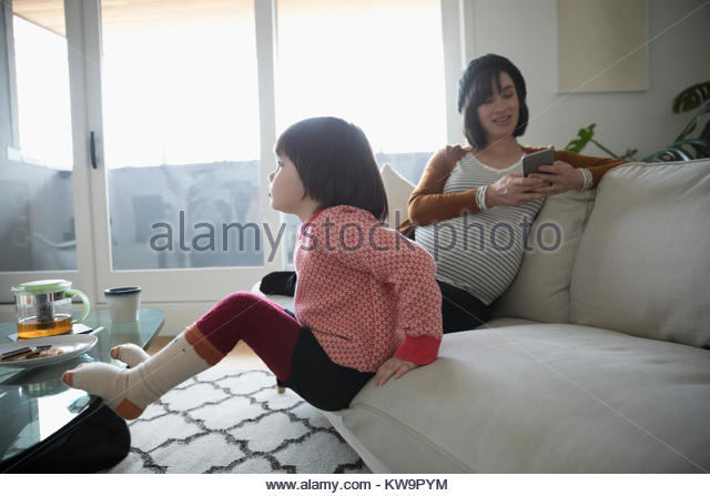 Pregnant mother and daughter on living room sofa - Stock Image