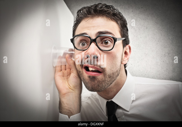 Office worker with glasses trying to hear through a wall - Stock Image