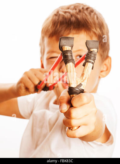 little cute angry real boy with slingshot isolated - Stock Image