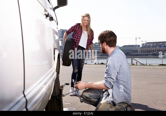 Smiling couple changing car tyre at minivan - Stock Image