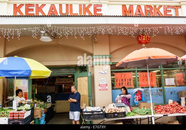 Honolulu Hawaii Hawaiian Oahu Chinatown Kekaulike Street produce market Asian woman man sale display - Stock Image