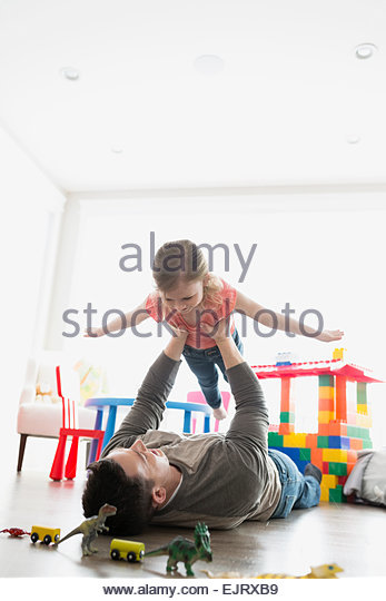 Father flying daughter overhead - Stock Image