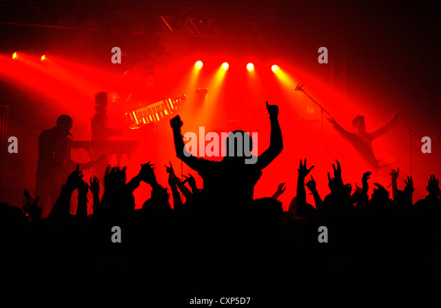 Silhouetted spectators and ambiance during live rock concert with rockers on stage illuminated by red spotlights - Stock Image