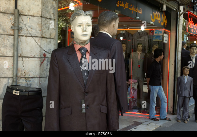 Manikin wearing western suit and tie with a broken nose and damaged head, chained to a pipe outside a shop in Tehran. - Stock Image