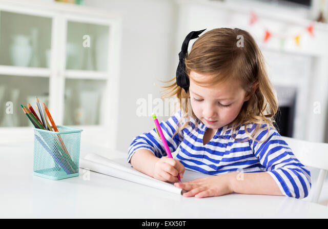 Girl (4-5) drawing in living room - Stock-Bilder