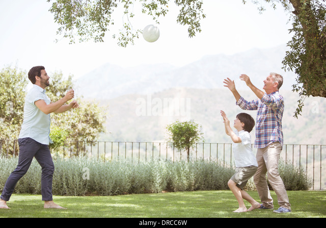 Multi-generation family playing volleyball in backyard - Stock Image