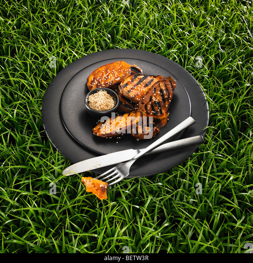 Barbecued sweet potato with sesame seeds on a black plate and a grass background. - Stock Image